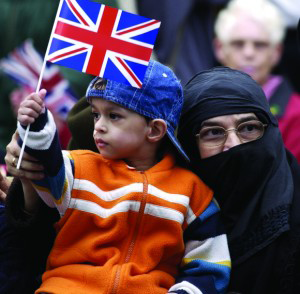 A photo of a British Muslim woman holding a union flag and wearing a niqab