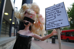 A photo of a disheveled barbie holding a placard