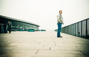 A photo of a lone man on a bridge